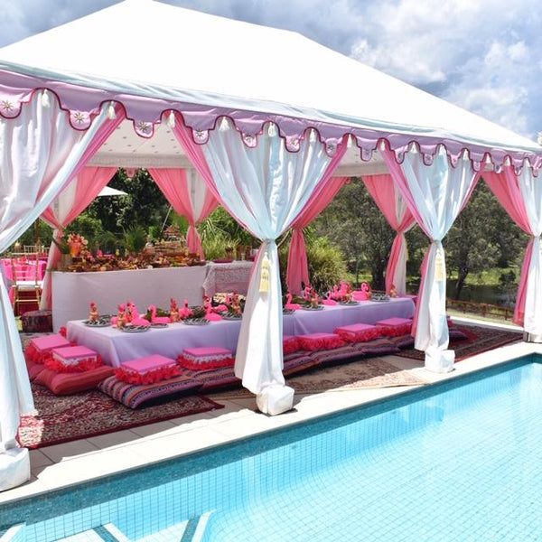 pink and white middle eastern marquee or garden tent next to a pool which is styled in pink for a children's party with low tables, grazing board, cushions