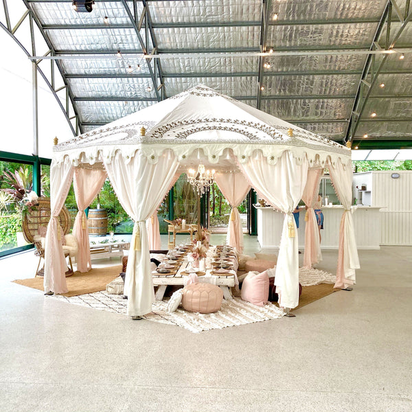 luxury tent pavilion in white with pretty pink styling on a low white table for a bridal party