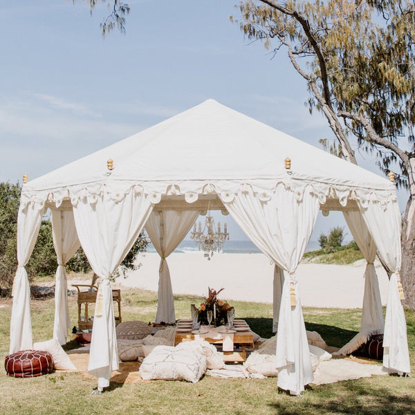 ladies bridal party at the beach under a white arabian bohemian marquee tent full of cushions and rugs with an exotic pop up picnic for hire on the gold coast