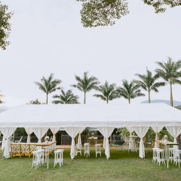 white wedding marquee with garden furniture and palms in the background
