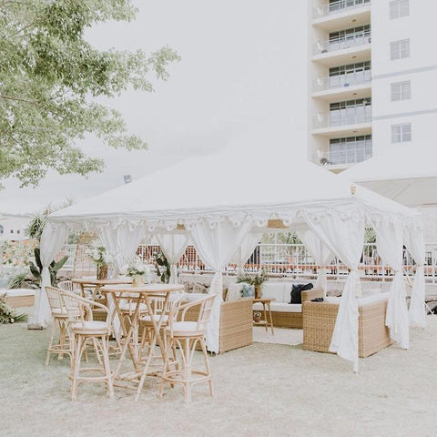beautiful white Arabian marquee filled with rattan cane furniture for a wedding or corporate cocktail area