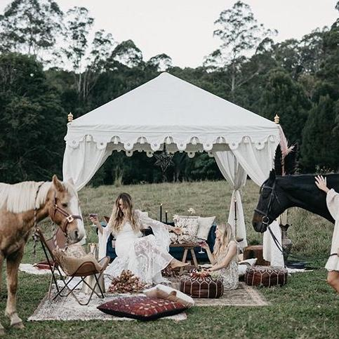 white bohemian tent in a field decorated with moroccan cushions and rugs with horses and brides