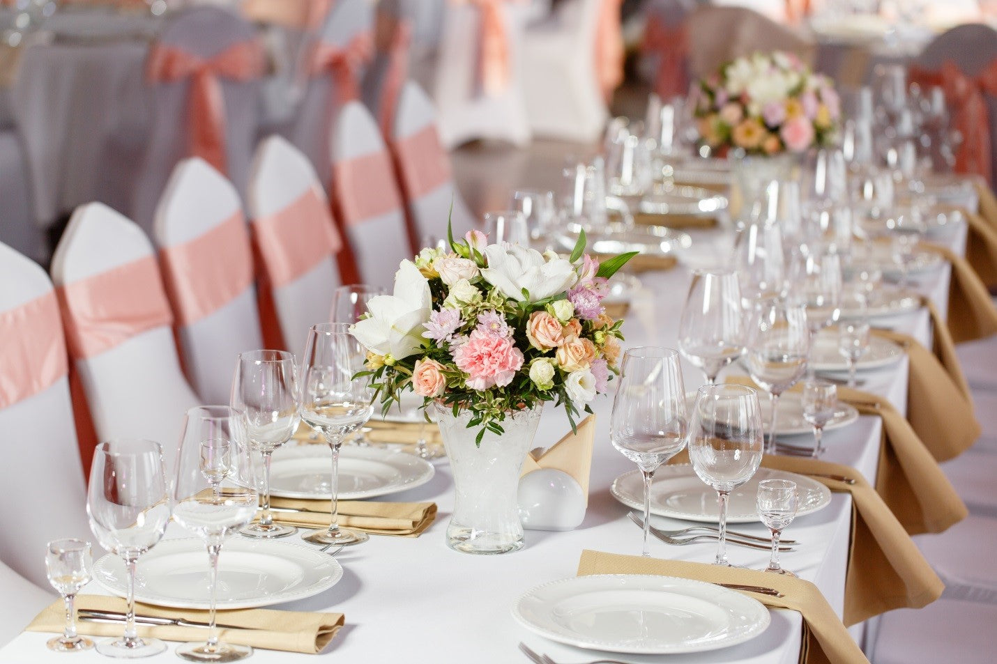 white tablecloths with white chair covers and pink chair sashes