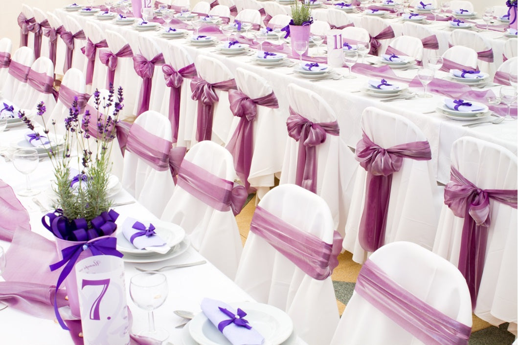 white banquet chair cover with purple organza sash