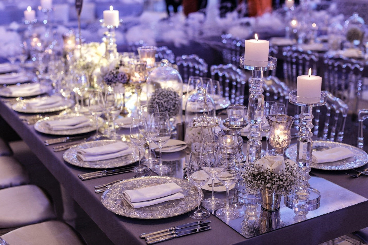 purple themed table setting with candle centerpieces