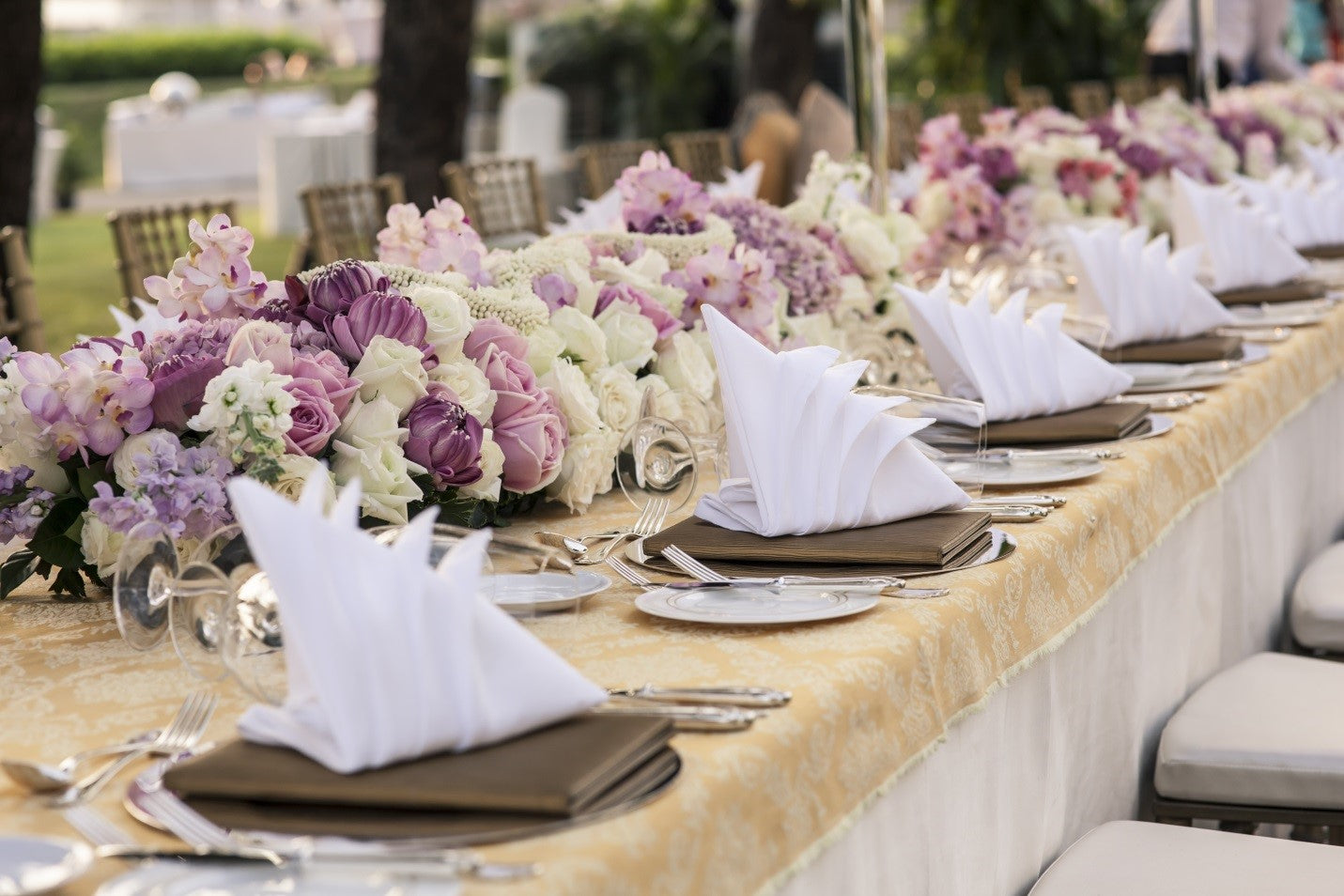 long banquet table with white tablecloth and flower centerpieces