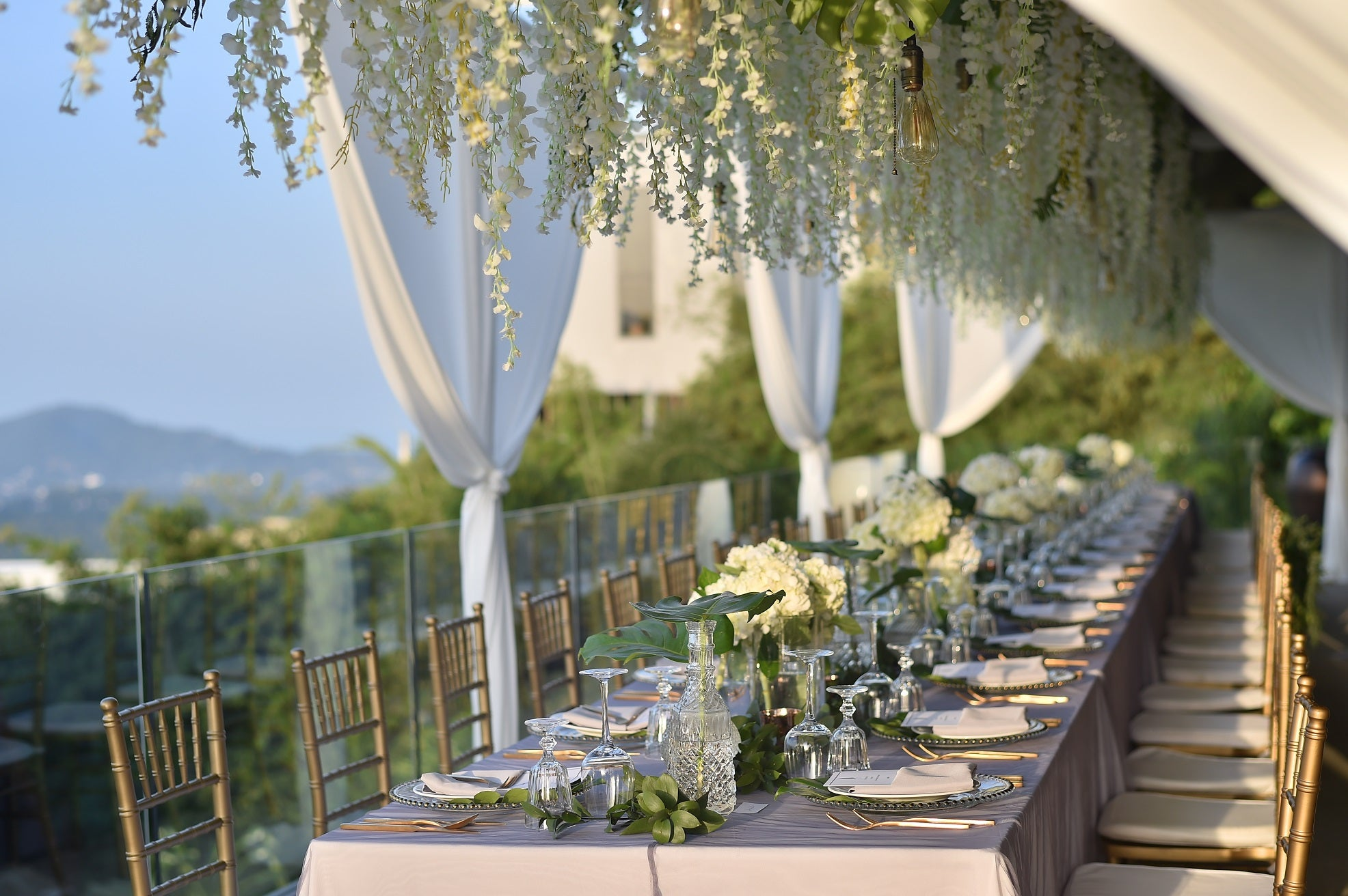 banquet table with tablecloths and glass flower vase centerpiece