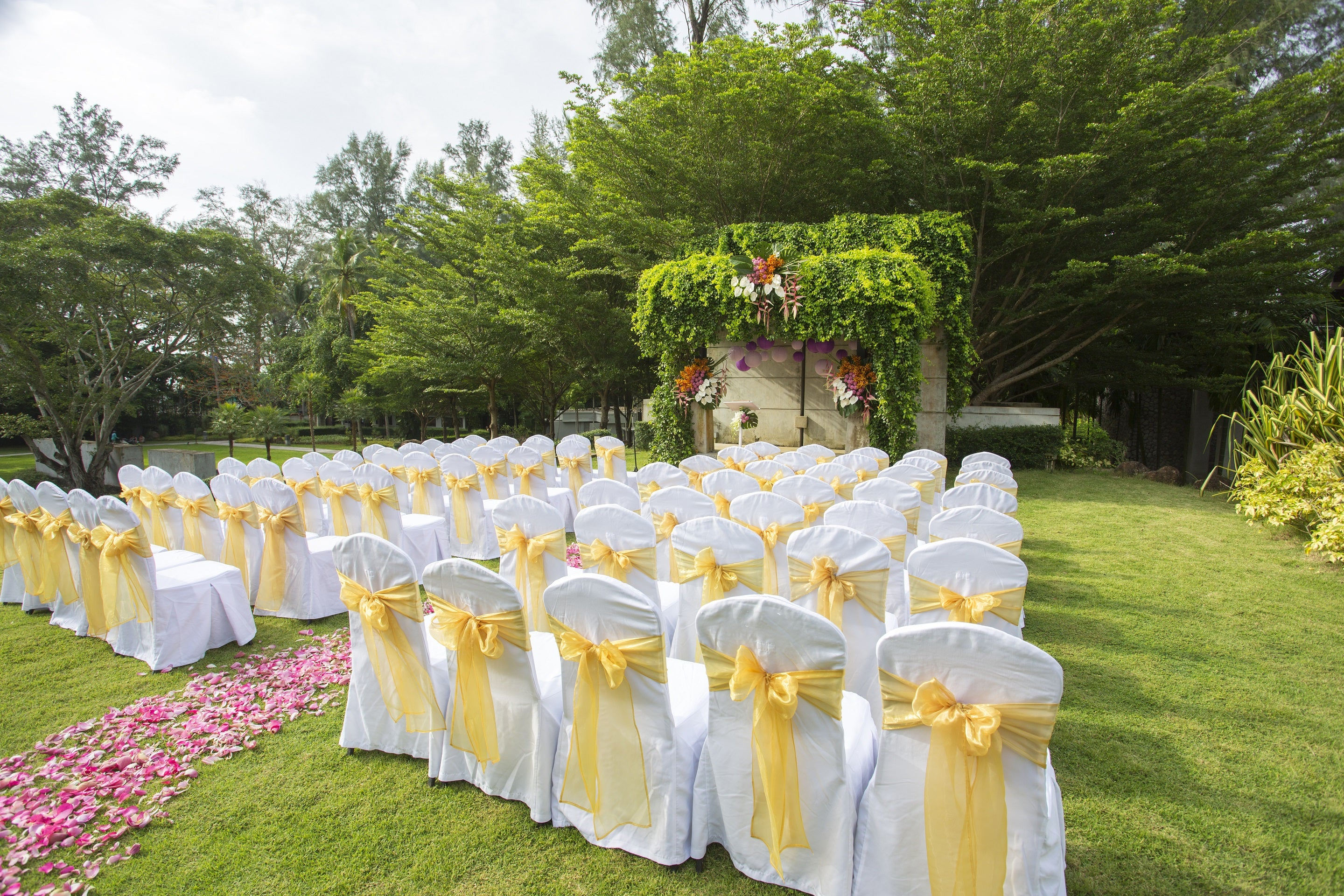 chair covers over chairs on grass at a wedding