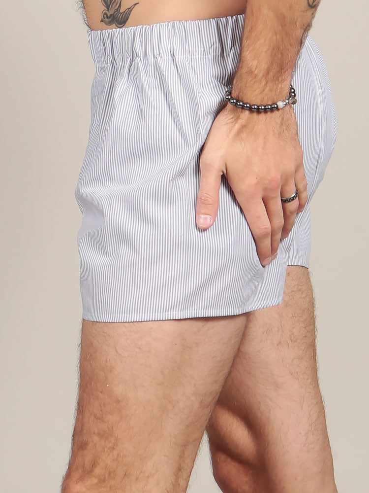 Side view of model wearing striped boxers in grey