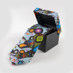 A tie in its box. The colourful print on the box top matches the print of the tie which is partially unrolled.