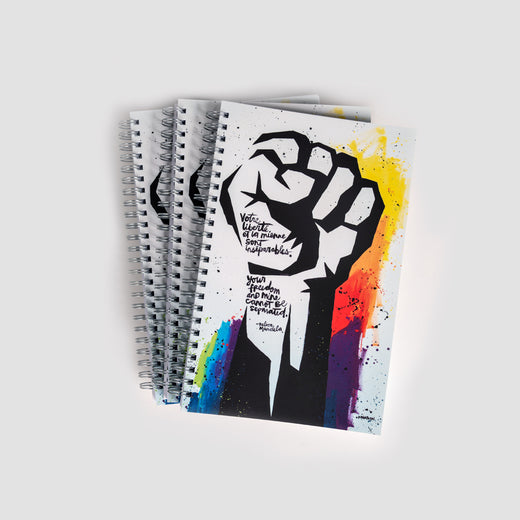 Three journals laid out featuring a stenciled image of a fist over a multicoloured background on the cover.