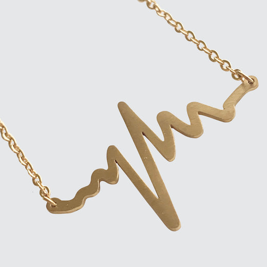 Gold necklace in the shape of a heartbeat on an EKG.