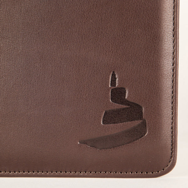 bottom right-hand corner of a leather portfolio featuring the Museum icon