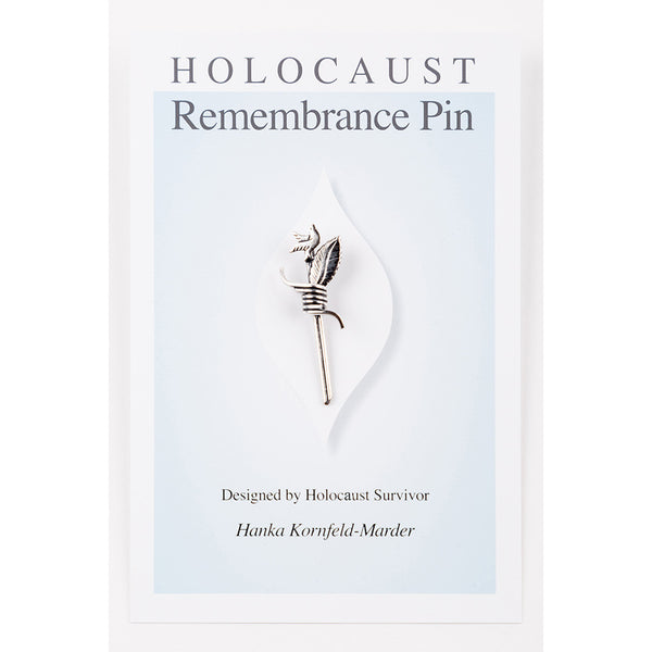 "Image of a pin against cardboard backing with the text ""Holocaust Remembrance Pin"" and ""Designed by Holocaust Survivor Hanka Kornfeld-Marder"