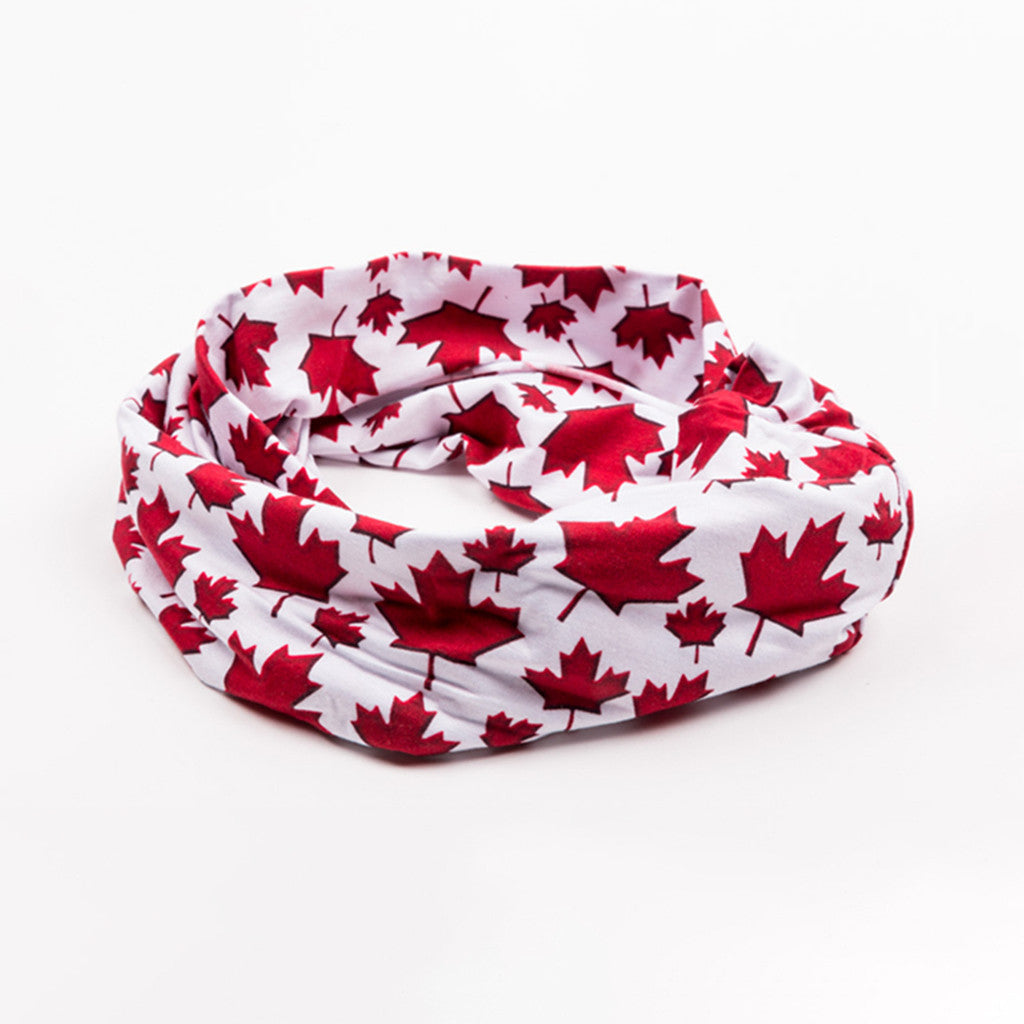 tubular headwear resting flat; its design features red maple leaves on a white background
