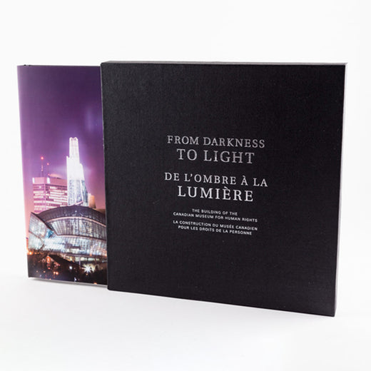 "Cover of a black slipcase and a book entitled ""From Darkness to Light""; the title appears in English and French."