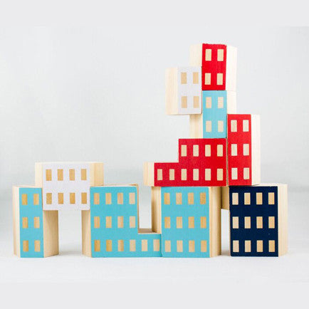 Ten painted wooden blocks that resemble buildings are piled up to form a cityscape