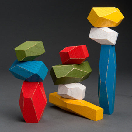 10 faceted wooden blocks balanced on top of each other to form three separate towers