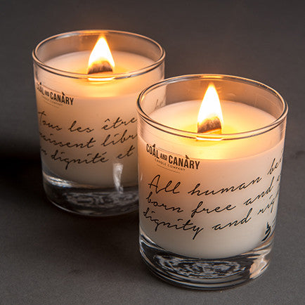 Two lit white candles with English and French writing etched on the glass containers.
