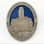 oval-shaped pewter-coloured pin featuring an image of the CMHR against a blue sky