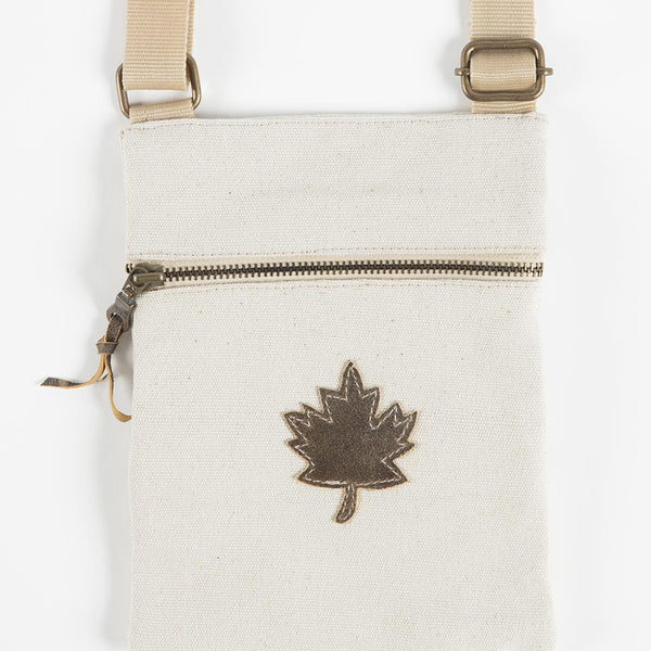 close-up of the front of the bag that shows the maple leaf as well as a horizontal zipper and the buckles for the adjustable strap