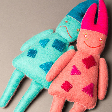two dolls made of felted wool laying side by side; one looks sad and the other looks happy