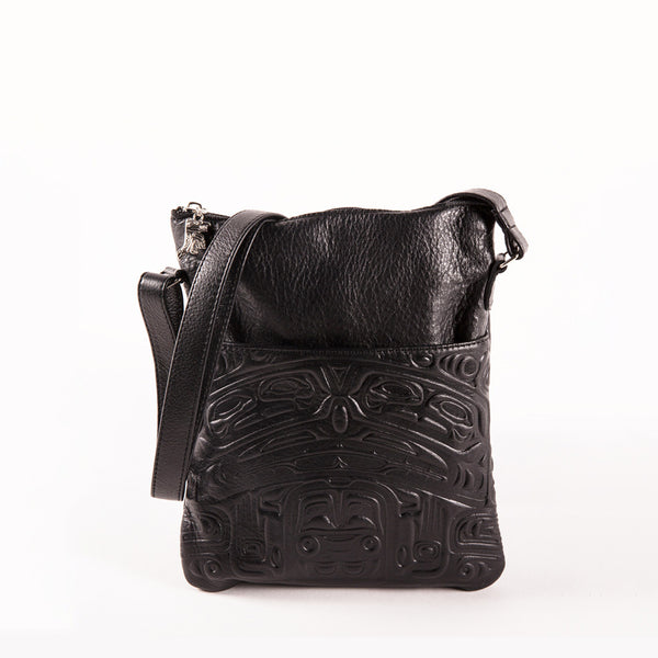black leather bag featuring an embossed design of a traditional indigenous bear image