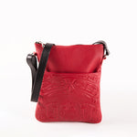 cherry leather bag featuring an embossed design of a traditional indigenous bear image