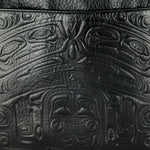 close-up of the traditional Indigenous bear design embossed on a black leather bag