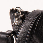 close-up of the zipper pull on a black leather bag