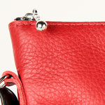 close-up of the zipper pull on a red leather bag