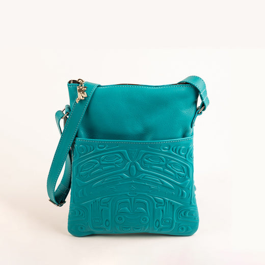 turquoise leather bag featuring an embossed design of a traditional indigenous bear image