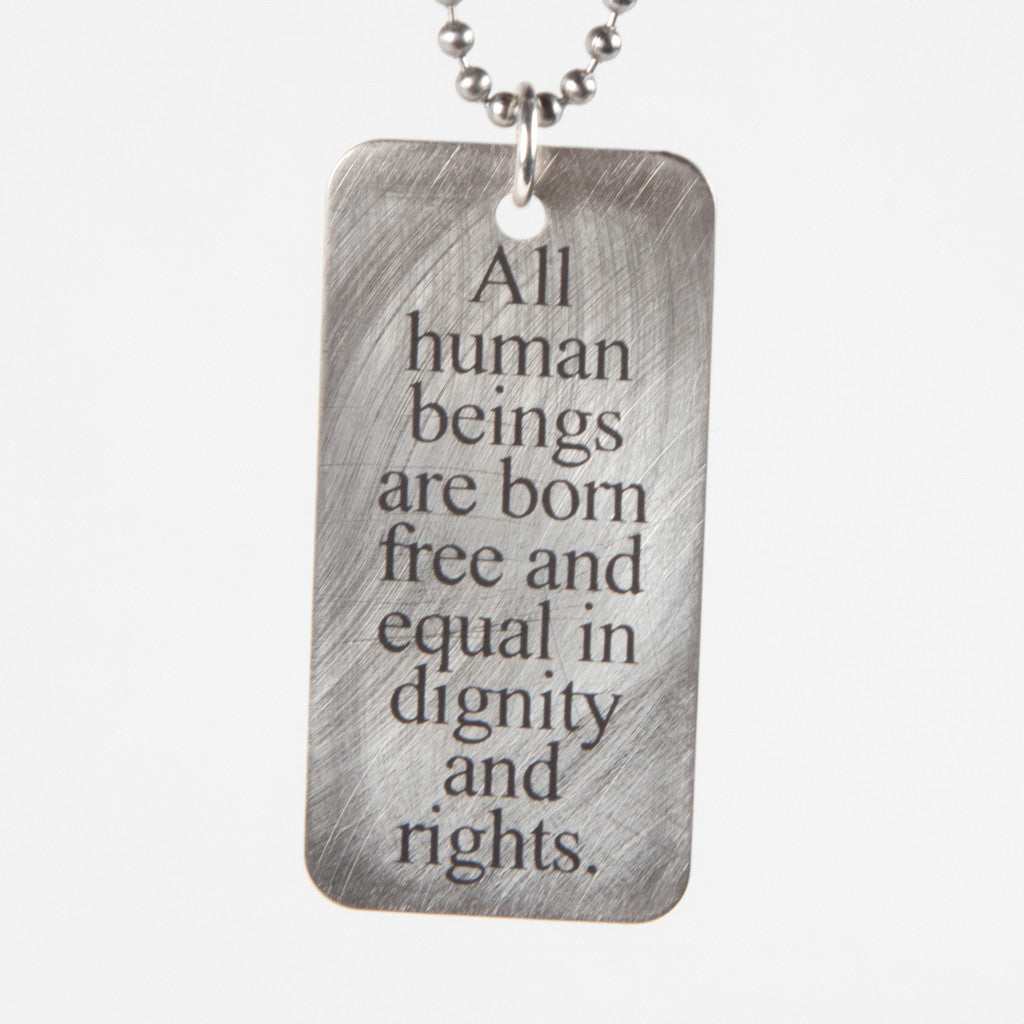"a steel pendant on a leather cord; the pendant reads ""All human beings are born free and equal in dignity and rights"""