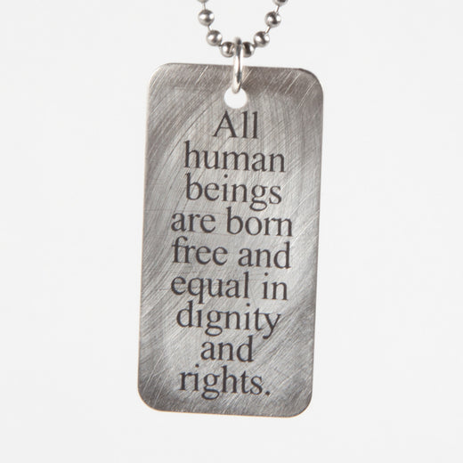 "a steel pendant on a cord; the pendant reads ""All human beings are born free and equal in dignity and rights"""