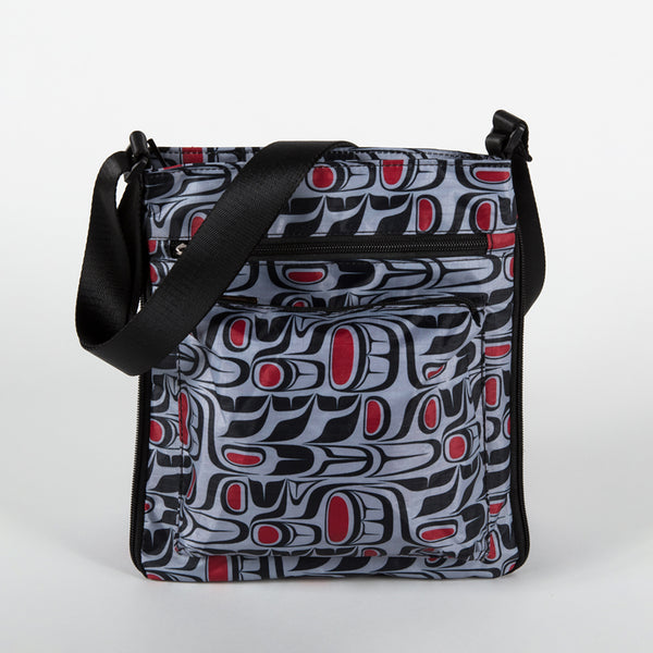 Cross-body bag featuring a red, blue and black pattern designed by Indigenous artist Paul Windsor