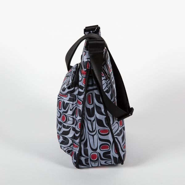 Profile of a cross-body bag featuring a red, blue and black pattern designed by Indigenous artist Paul Windsor