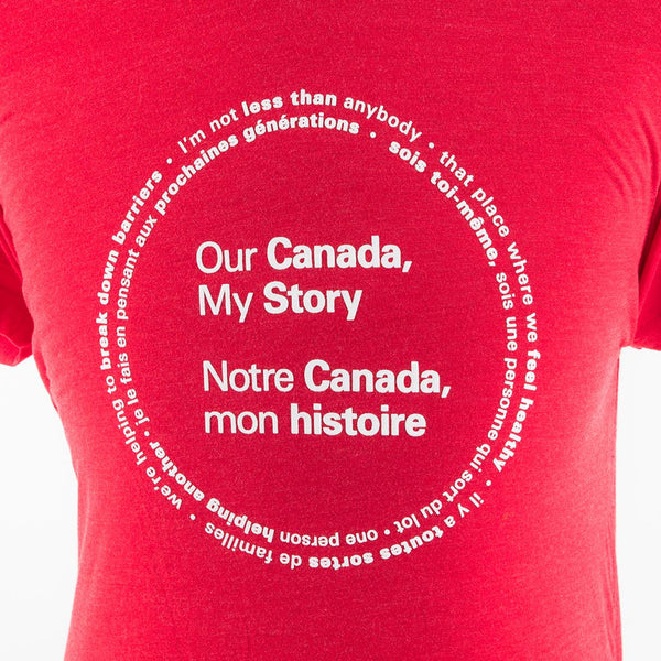 "a close-up of the front of the shirt and the text ""Our Canada, My Story,"" and ""Notre Canada, mon histoire,"" printed in white; a circle composed of two lines of text surrounds the main text"