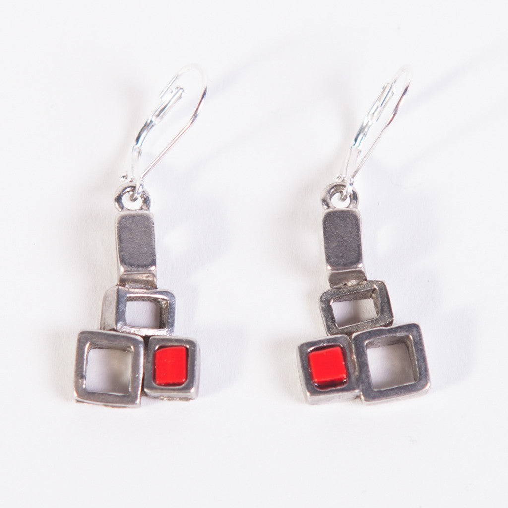 a set of earrings composed of linked pewter block-shaped pieces; squares are cut-outs, solid or filled with red-coloured glass