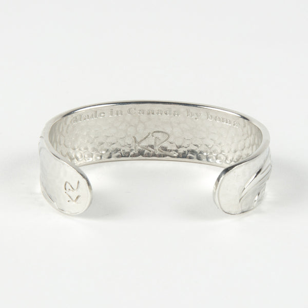 back view of a silver-coloured bangle featuring a design of a hummingbird