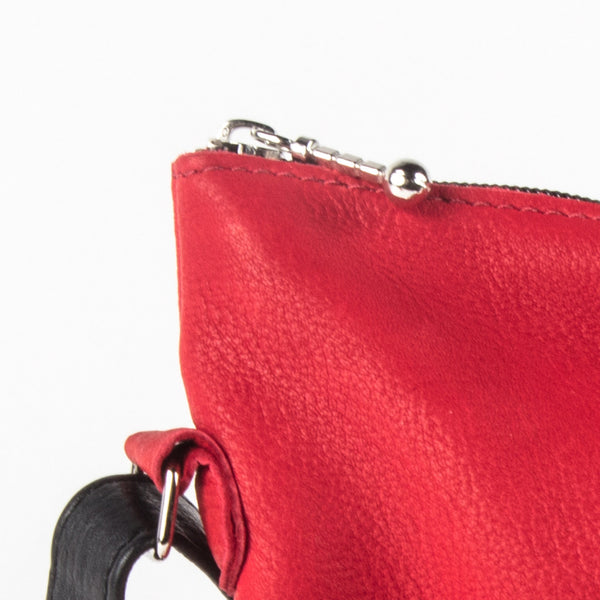 close-up of a zipper pull on a red leather bag