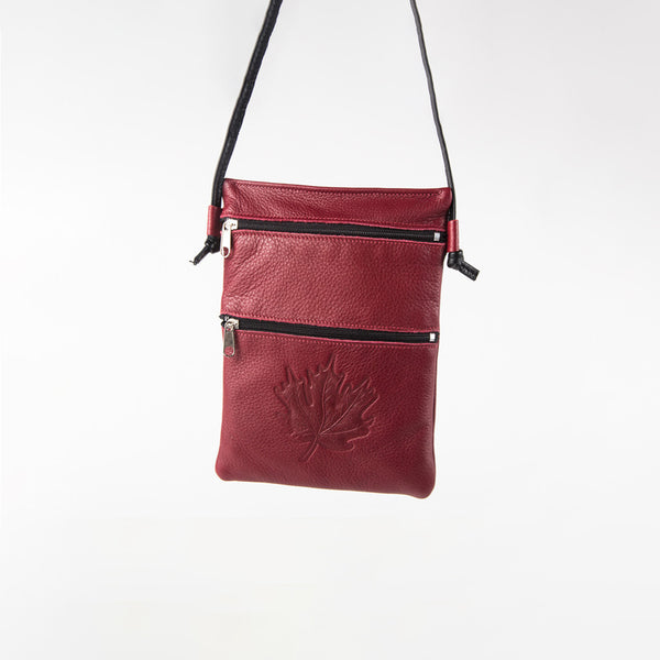 leather bag with a maple leaf design and two zippers