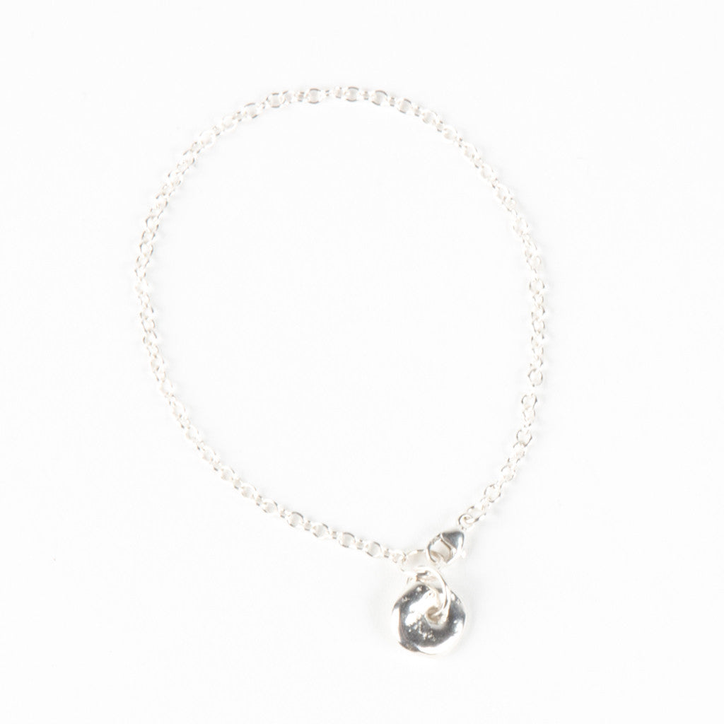 a silver chain bracelet featuring a stone with a hole