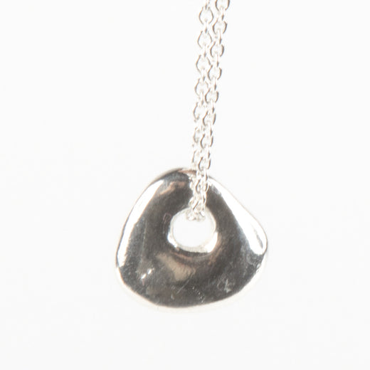 a silver stone pendant featuring a hole