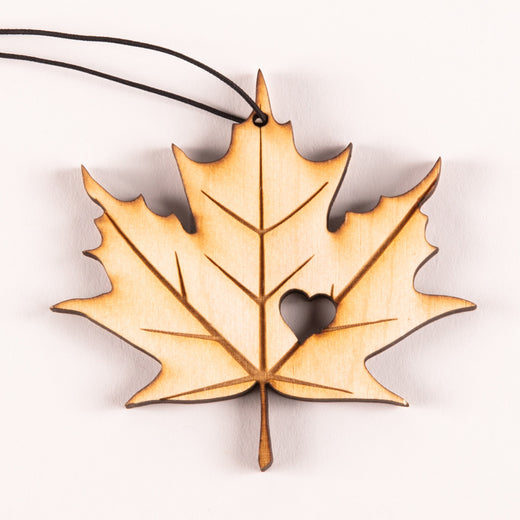 A laser-etched wooden ornament featuring a maple leaf with a heart cut-out