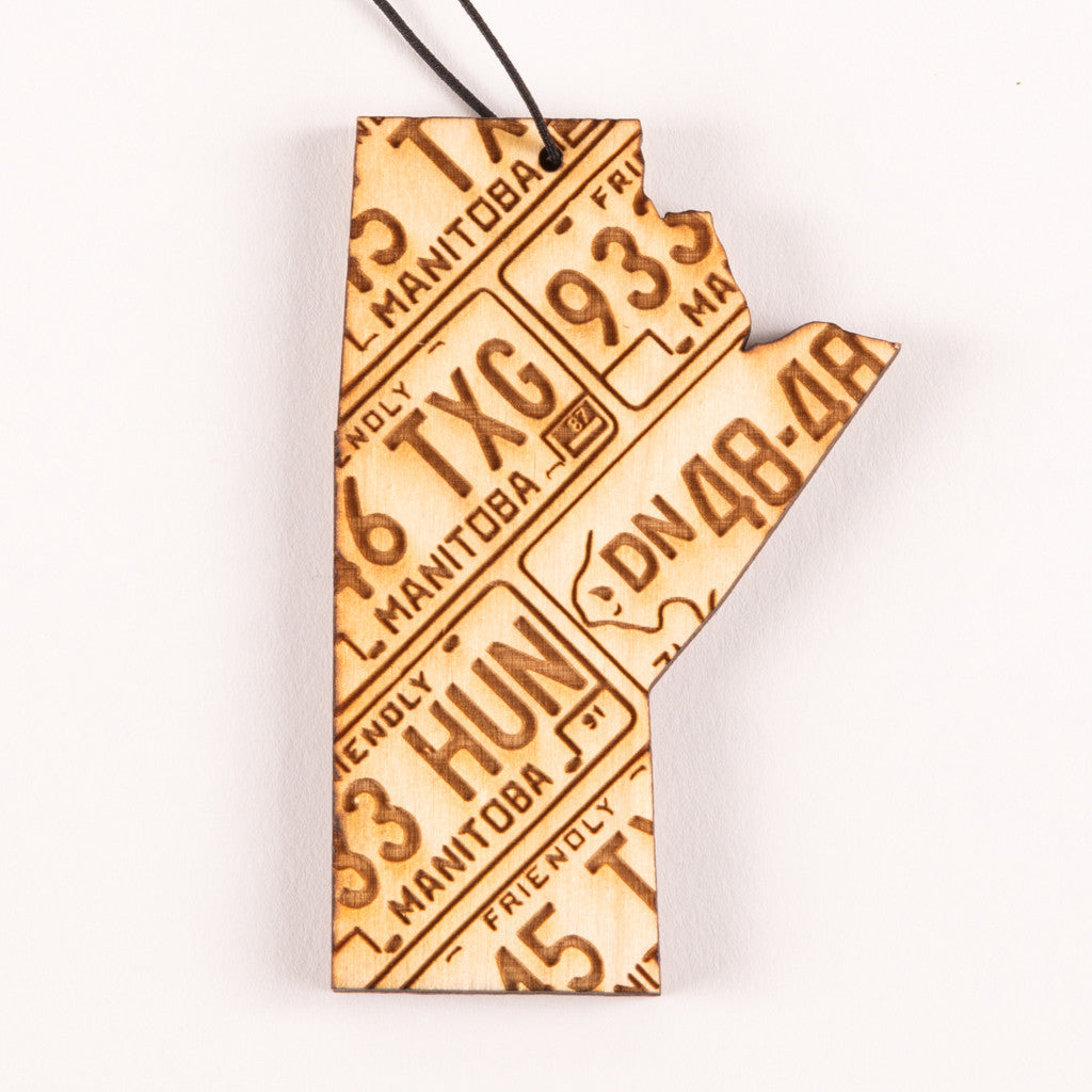 a laser-etched wooden ornament featuring the design of the shape of the province of Manitoba; Manitoba licence plates are also featured as a pattern on the ornament