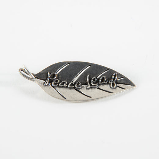 "Leaf-shaped charm with the text ""Peace Leaf"""