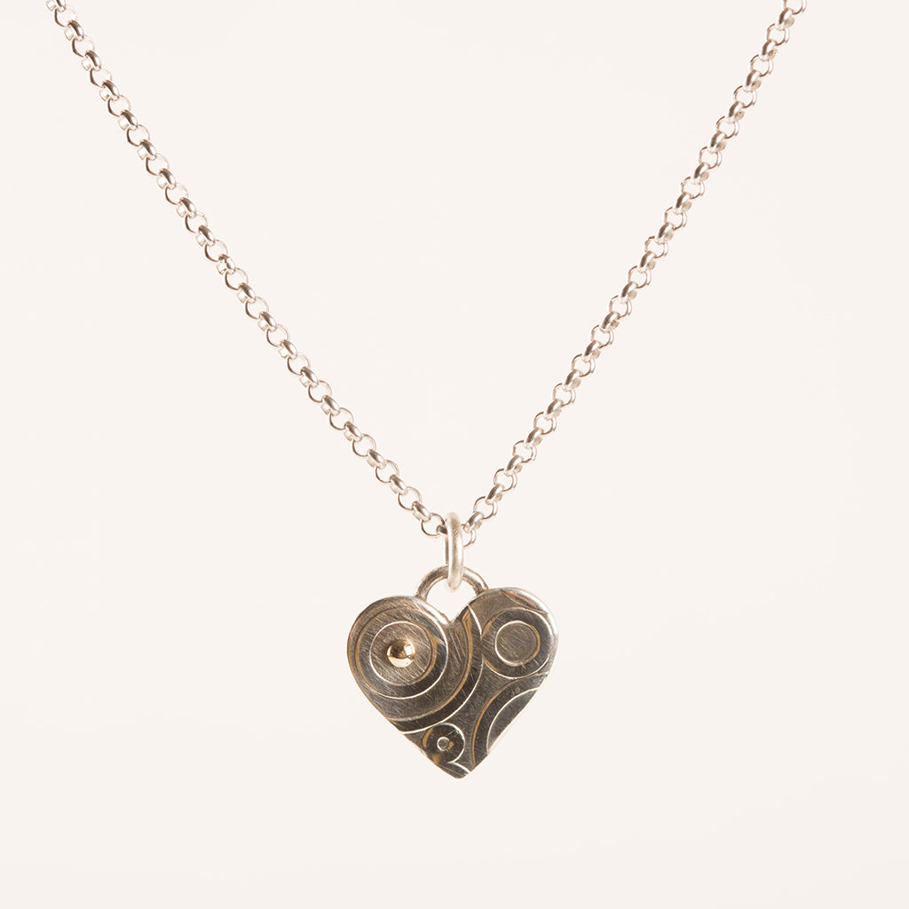 silver heart-shaped pendant on a chain