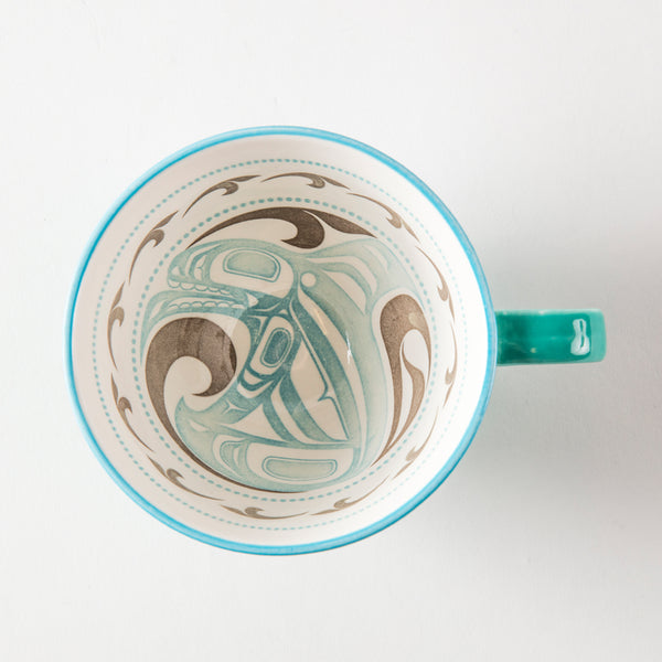 Interior of a turquoise mug featuring artwork of a killer whale