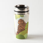 "White, green and brown travel mug featuring ""Sasquatch"" artwork by Indigenous artist Francis Horne Sr."