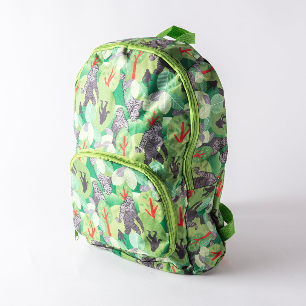 green and brown backpack featuring a patterned print of sasquatch in the forest